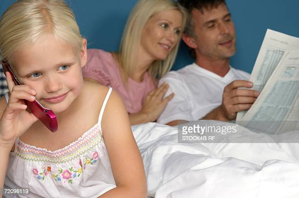 Little blond girl is phoning in front of the bed of her parents, selective focus