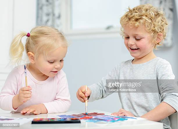 A little blond girl looks at her brothers painting