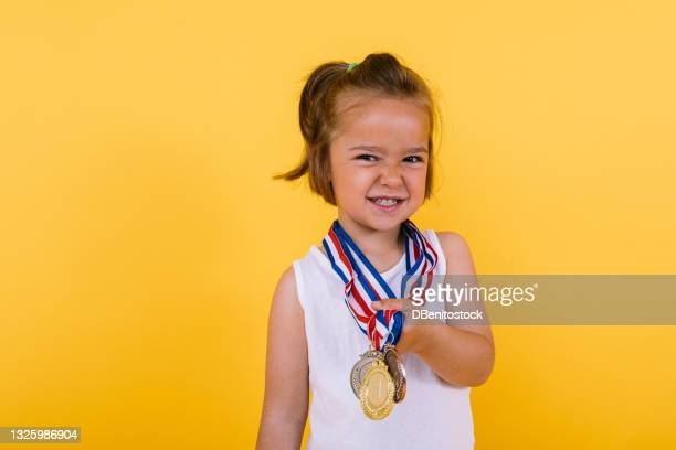 little blond girl of caucasian ethnicity, showing her sports medals, on a yellow background. olympics and sports triumph concept - medallist stock pictures, royalty-free photos & images