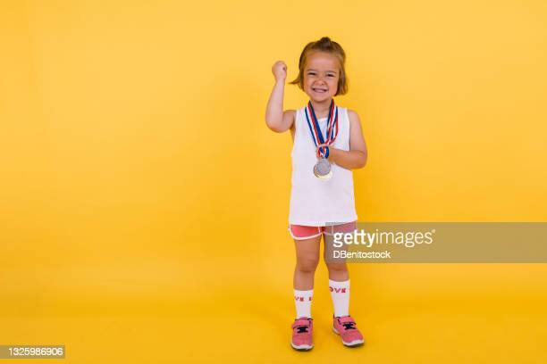 little blond girl of caucasian ethnicity, showing her sports medals and clenching her fist, on yellow background. olympics and sports triumph concept - medallist stock pictures, royalty-free photos & images