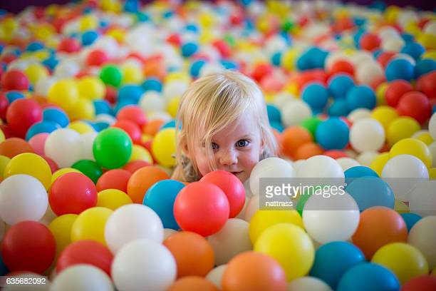 Little blond girl plays in a ball pool