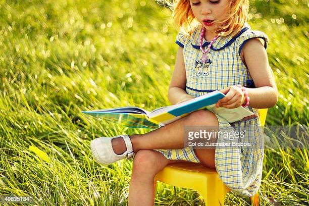 Little blond girl sitting in nature reading a book