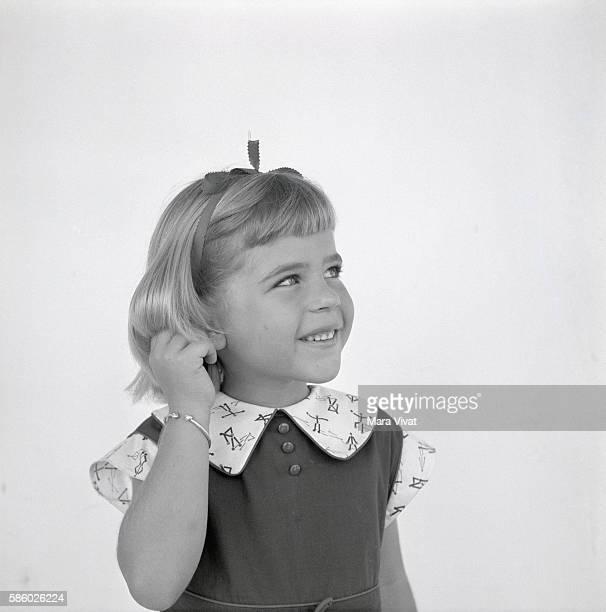A little blond girl touches her ear Jamaica