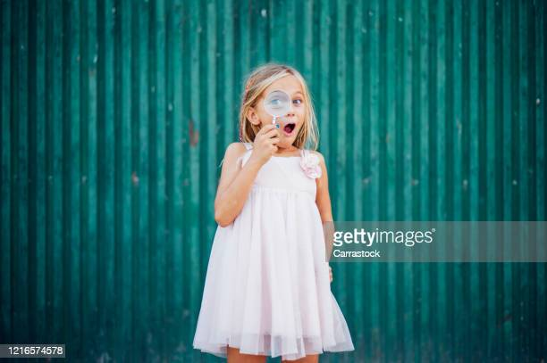 little blond girl with blue eyes and magnifying glass - lupa fotografías e imágenes de stock
