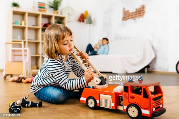 little blond playing with a wooden fire truck - primary age child stock pictures, royalty-free photos & images
