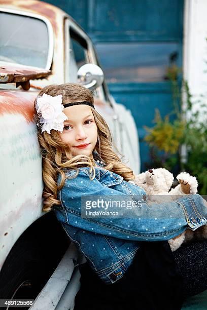 Petite fille en voiture d'époque avec ours en peluche