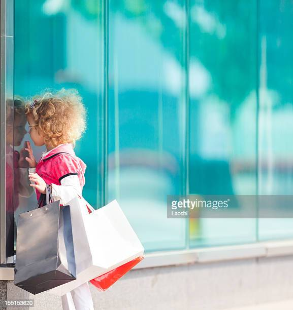 Little blonde girl with bags on arm window shopping