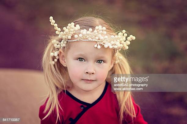 Little blonde girl with white berries on head