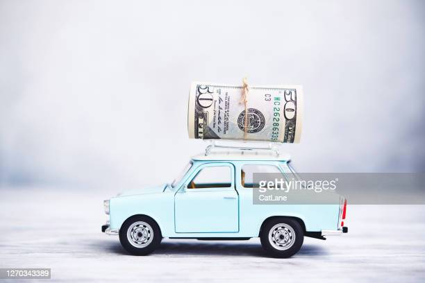 little blue car with cash roll on roof rack - expense stock pictures, royalty-free photos & images