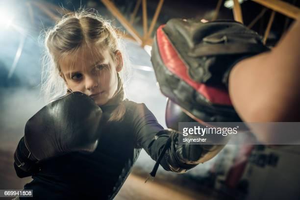 Petit boxeur ayant une formation avec son entraîneur méconnaissable dans un gymnase de sportive.