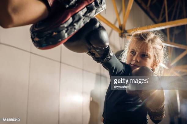 Little boxer having a sports training with her unrecognizable coach in a gym.
