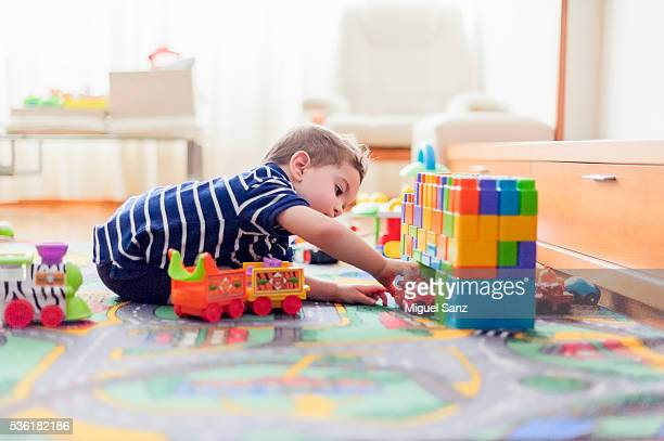 little boy, 2 years, playing with small cars and toys at home - juguete fotografías e imágenes de stock