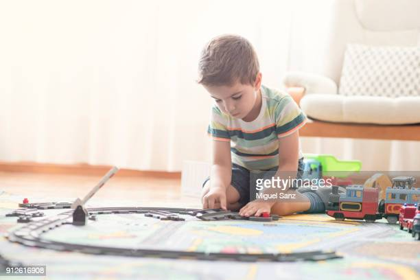 Little boy, 3-4 years, playing with train and toys at home