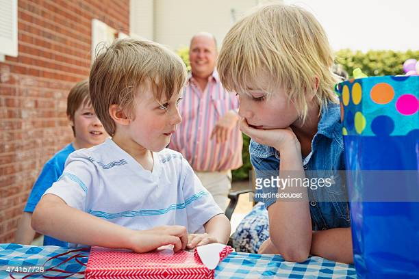 "little boy about to open his birthday presents outdoors. - ""martine doucet"" or martinedoucet stock pictures, royalty-free photos & images"