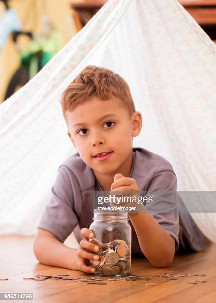 Little boy adding coins to jar full of money laying down under tent made from bed sheet.