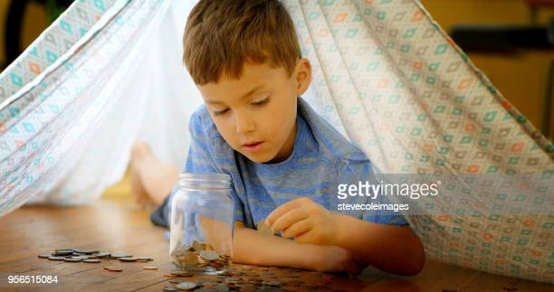 little boy adding coins to jar. - finance and economy stock pictures, royalty-free photos & images