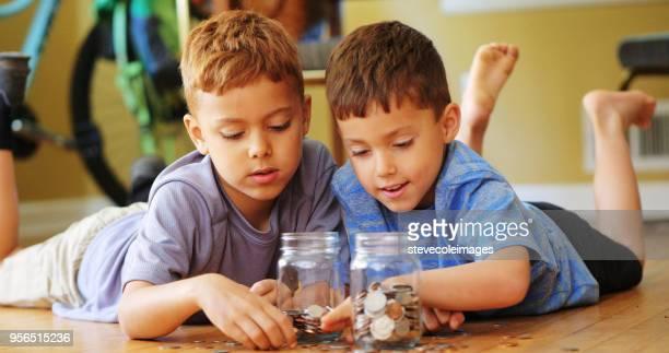Little boy adding coins to jar.