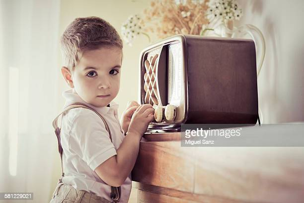 Little boy adjusting and listening vintage radio