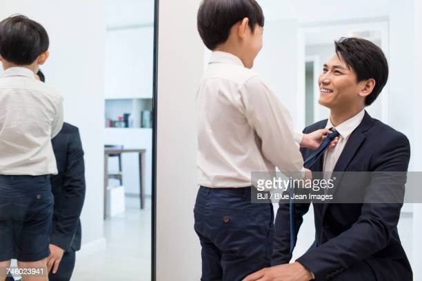 Little boy adjusting fathers tie