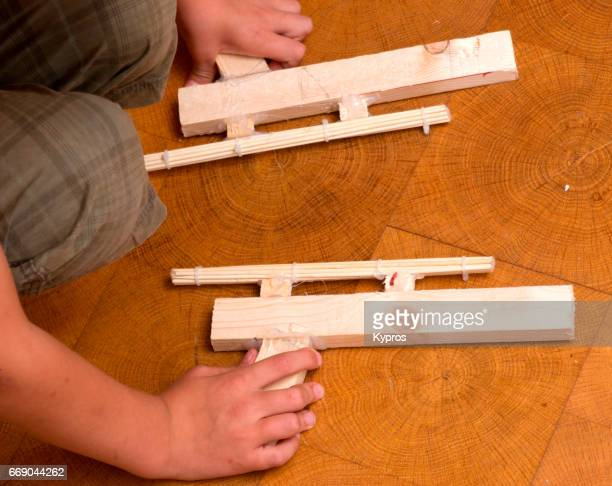 Little Boy Age 7 Years Holding Wooden Toy Guns