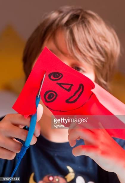 Little Boy Age 8 Years Drawing Faces On Red Paper With Felt Marker Pen