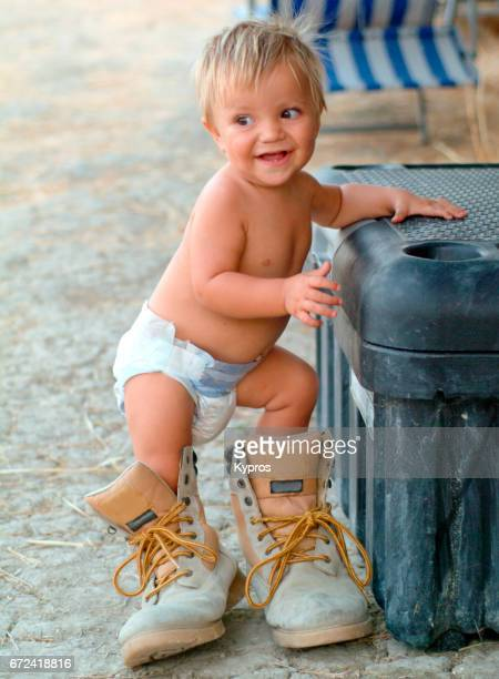Little Boy Age One Year Wearing Father's Work Boots