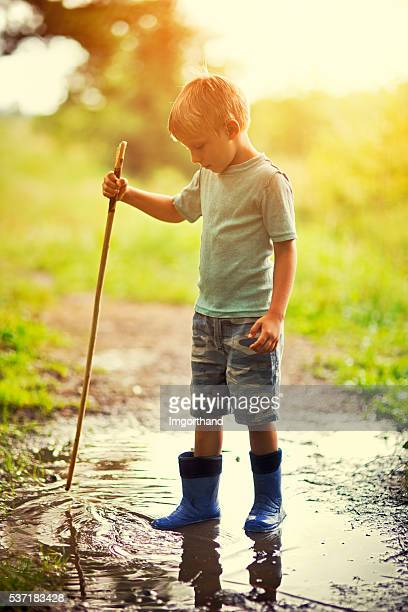 Little boy aged 4 playing in puddle