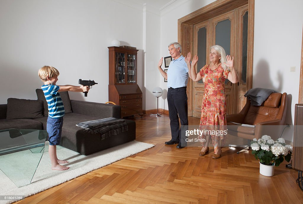 Little boy aiming with toy gun towards grandparents at home : Stock Photo