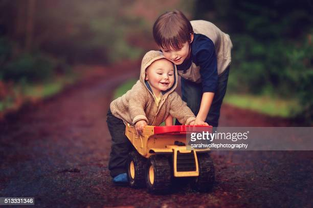 Little boy and a baby pushing a dump truck together