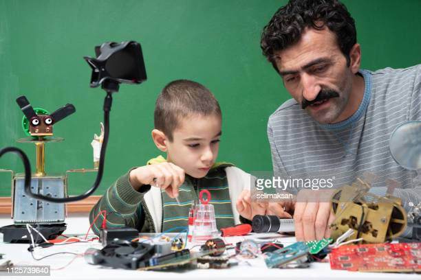 Little Boy And Adult Man Working On Robotics
