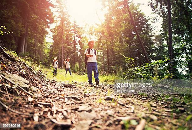 Little boy and family his hiking in forest