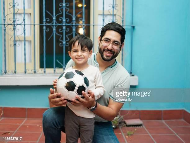 futebol da terra arrendada do rapaz pequeno e do pai e sorriso na câmera - latino americano - fotografias e filmes do acervo