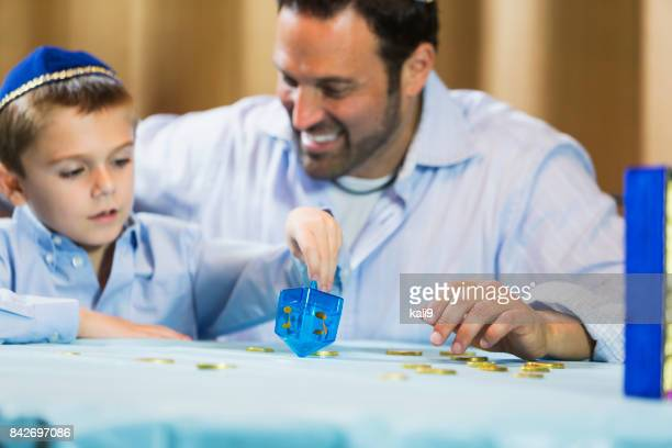 little boy and father playing dreidel - dreidel stock photos and pictures