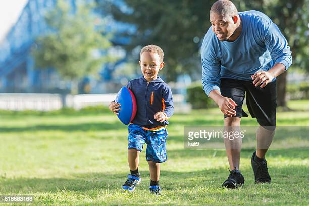Little boy and father playing in the park with ball