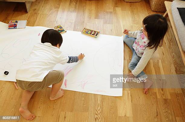 Little boy and girl drawing a picture in the room