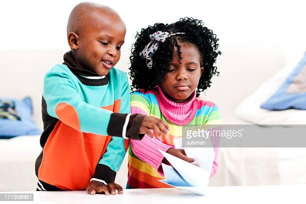 Kleine Jungen und Mädchen Falten mit Papier Boot