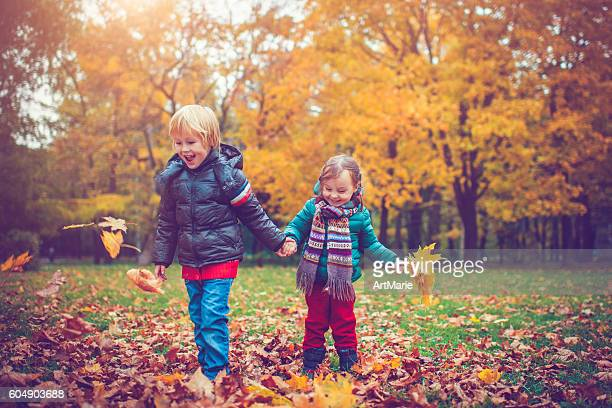 Little boy and girl in autumn park