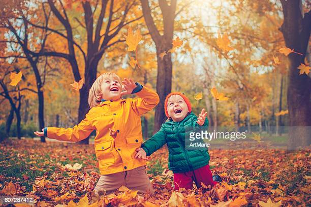 little boy and girl in autumn park - young leafs stock photos and pictures