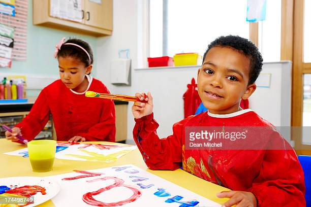Little boy and girl painting in playschool