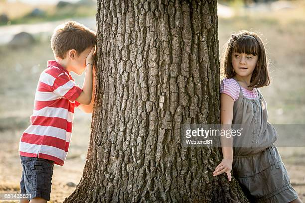 Little boy and girl playing hide and seek in nature