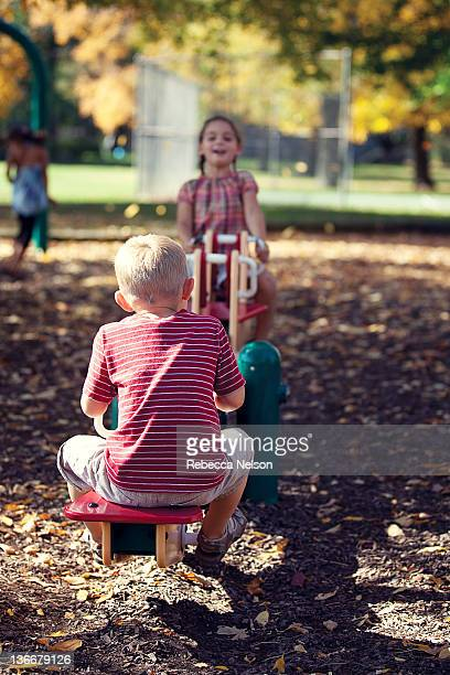 Little boy and girl playing on seesaw