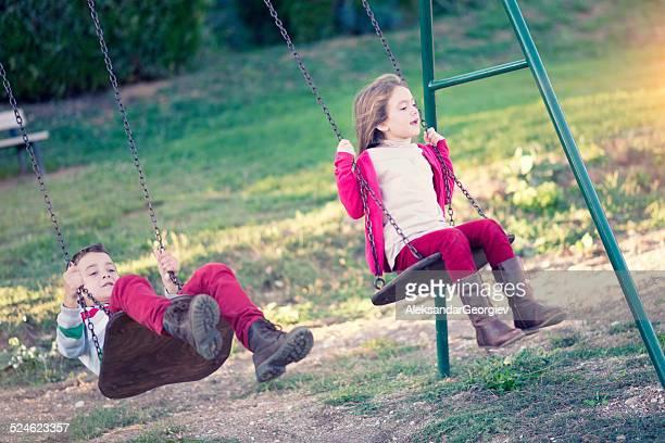 Kleine Jungen und Mädchen spielen auf Schaukel im Park