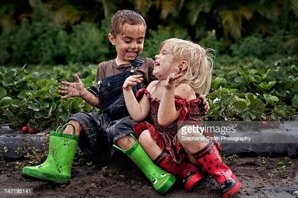 little boy and girl playing - schmutzig stock-fotos und bilder
