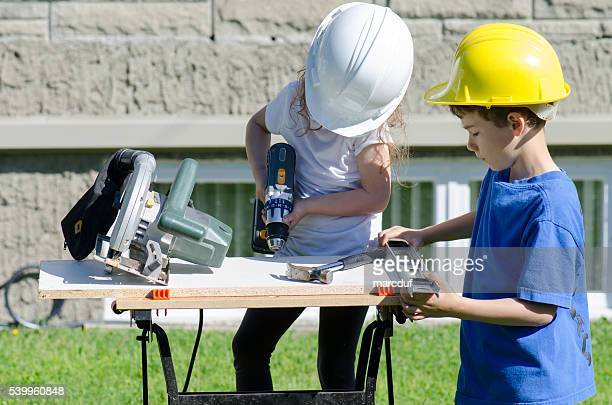 Little boy and girl playing with big tools outside