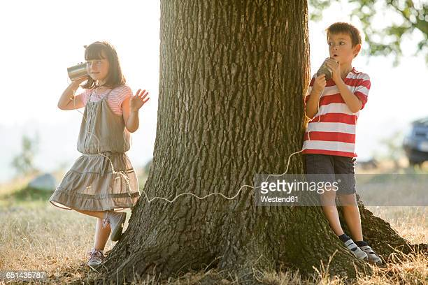 Little boy and girl playing with tin can phone in nature