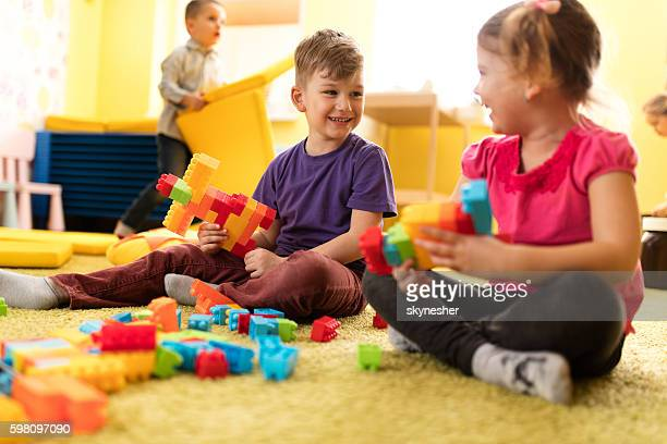 Little boy and girl playing with toy blocks at preschool.