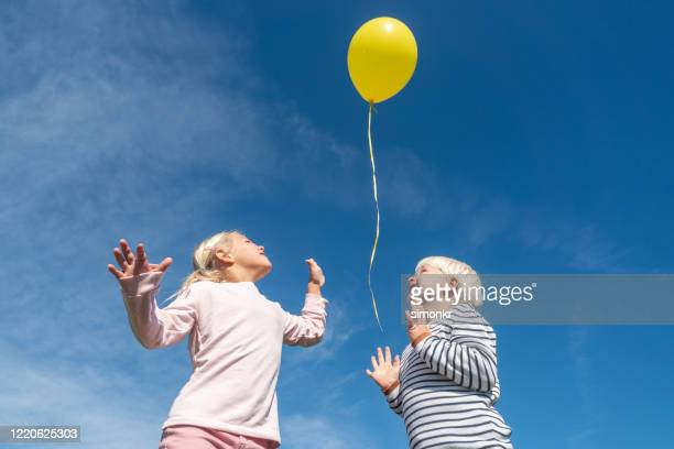 little boy and girl releasing balloon in blue sky - printed sleeve stock pictures, royalty-free photos & images