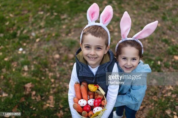 petit garçon et fille montrant leurs trophées après une chasse réussie d'oeuf de pâques - chasse aux oeufs de paques photos et images de collection