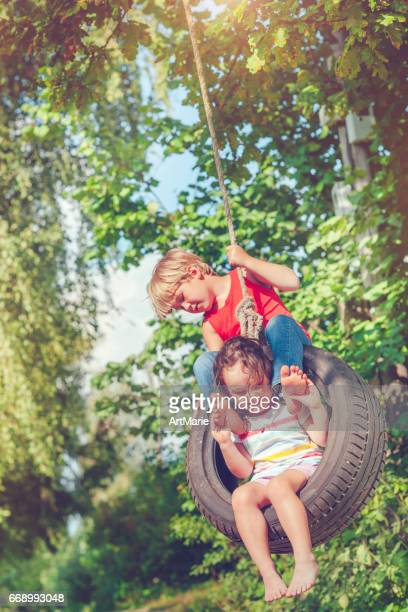 Little boy and girl swinging in summer