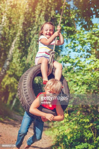 little boy and girl swinging in summer - little russian girls stock photos and pictures